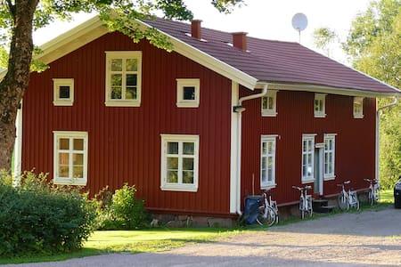 Edvinshuset, rött timmerhus med vita knutar - Lerbäcksbo