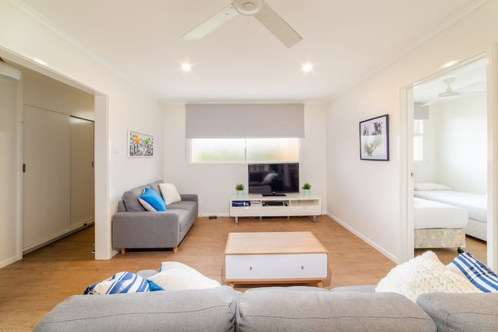 Living area with air-conditioning, fans and view of 3rd bedroom with 2 single beds