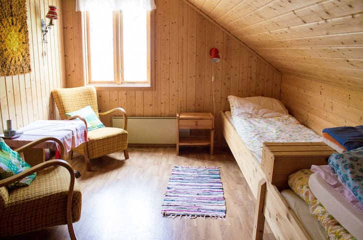 Soverom med to senger og sitteplass // Bedroom with two single beds and chairs