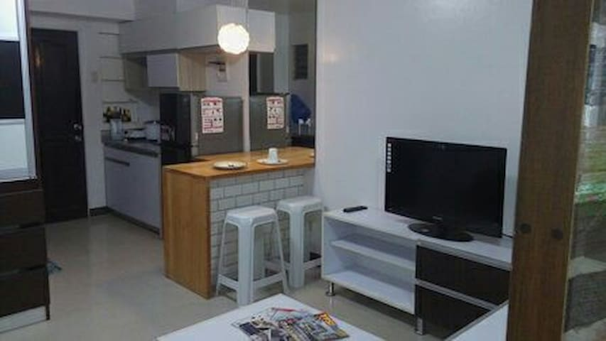Breakfast nook beside TV, behind is the small kitchen sink and stove