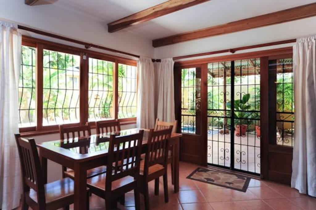 Large dining area overlooking pool and garden.