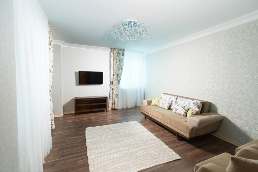Вместительная и уютная гостиная с мягкой зоной и телевизором