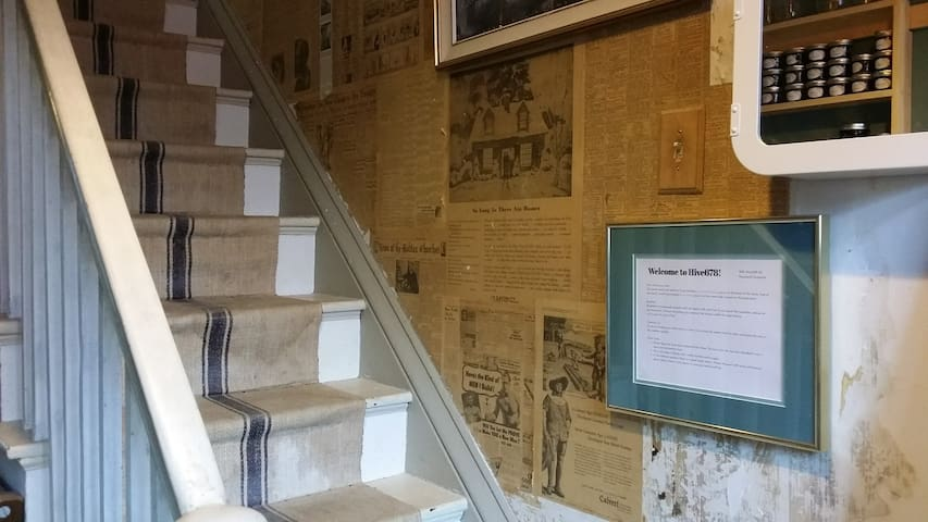 The first thing you'll see as you enter is the antique grain sack cloth stair runner, and authentic wartime newspaper wall. You'll either love it or hate it.