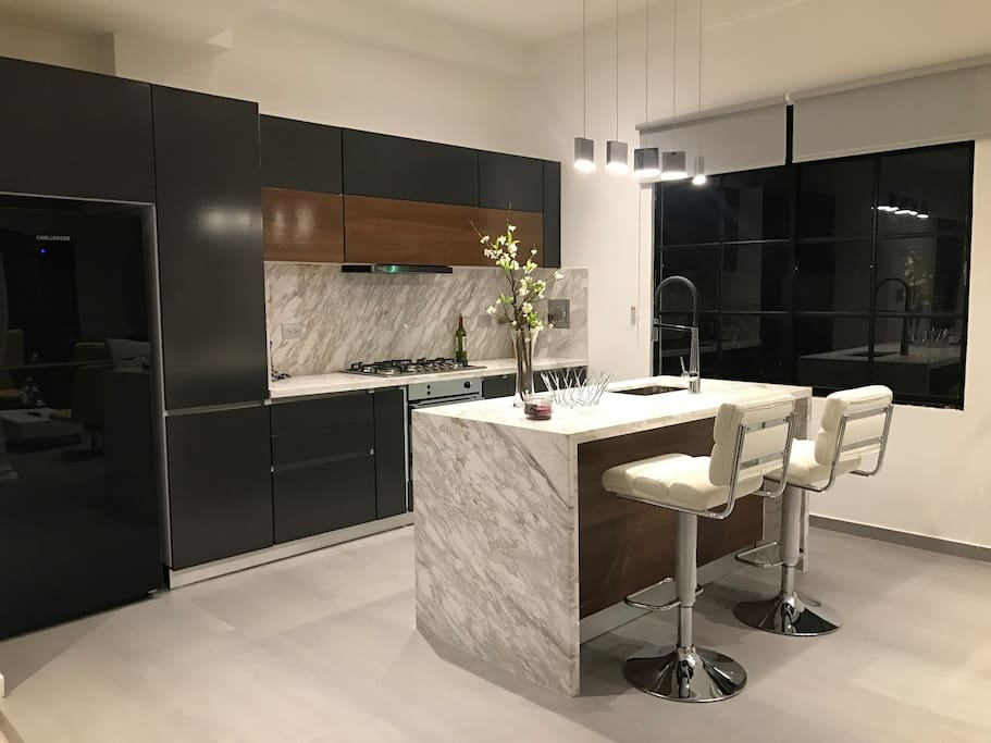 Luxury brand new designer kitchen with top of the line appliances and marble countertops.
