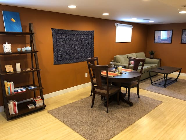 Bookshelf, dining table and couch/TV area.