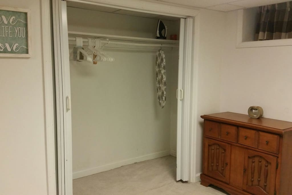 Plenty of closet room with hangers, an iron and ironing board.
