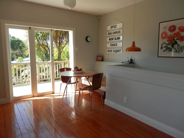 Kitchen with round table, bench seat and doors leading to back deck