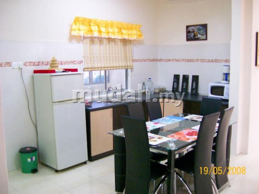Well-equiped kitchen with refrigerator and washing machine.