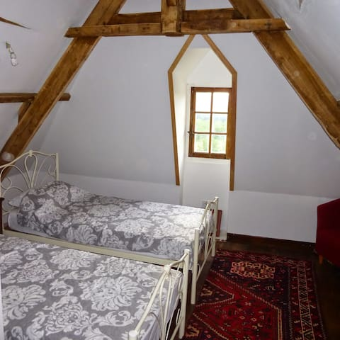 Twin bedroom accessed by a spiral staircase, overlooking the river. It has its own small shower room/wc