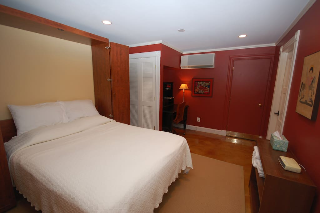 Queen sized bed, located at the back of the main room. Writing desk is next to the bed. The red painted door leads to the back room with the 2 twin beds