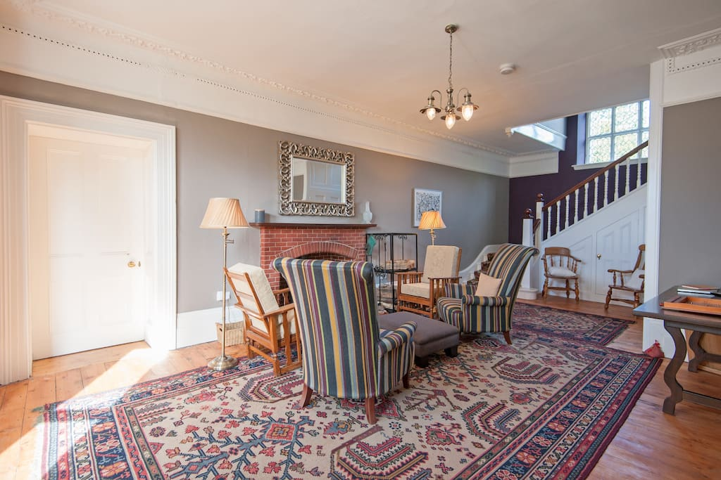 The hall with woodburner, comfy chairs and space at the table for games and puzzles