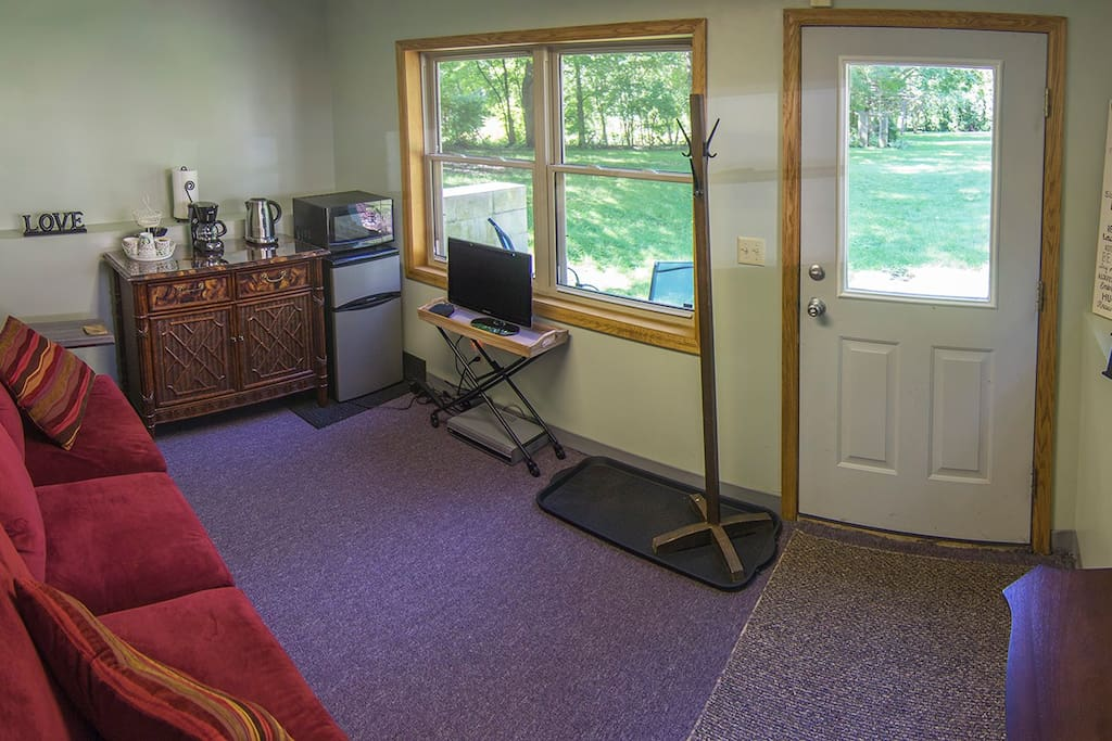 Living Room Cafe with windows for great view of yard and fresh air, also fireplace heater for ambiance extra warmth in winter months. It has a refrigerator, microwave, coffee maker, & hot water pot. All windows have blinds or curtains for privacy and room darkening.