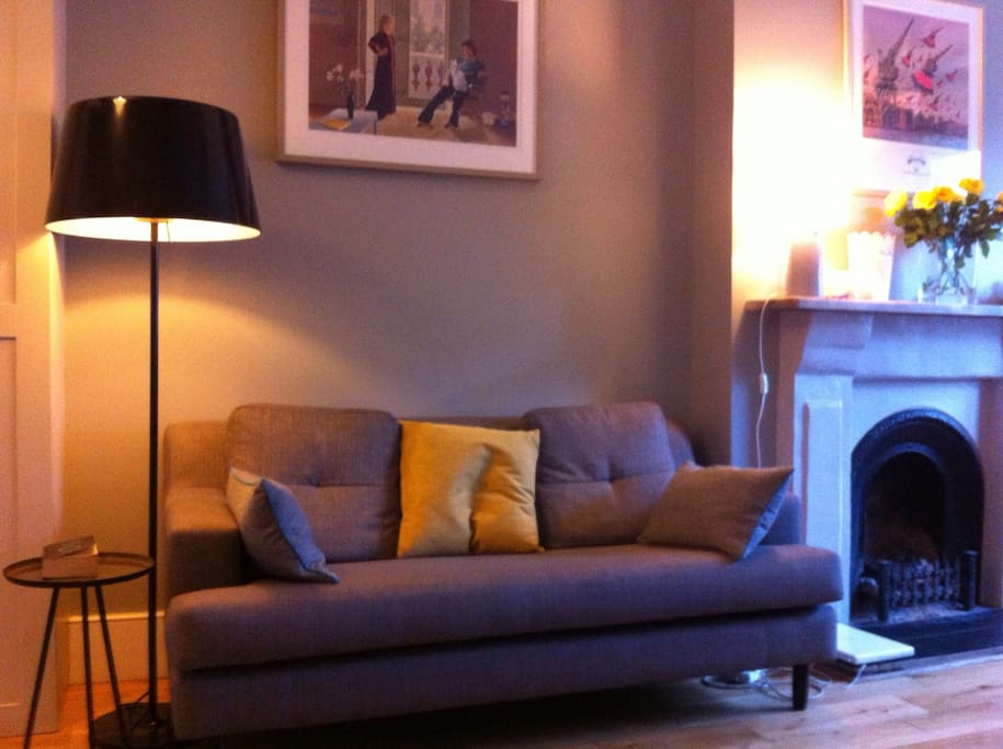 Lounge furnished in muted Farrow & Ball grey tones. Features include two sofas, fire place, solid oak floors, coffee table, flat screen TV with BT TV