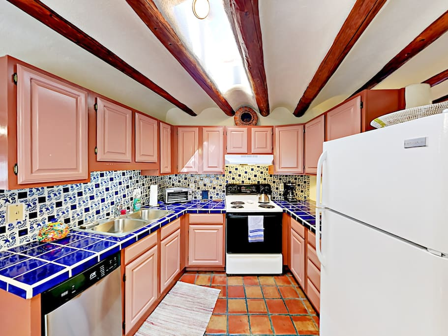 The well-equipped kitchen features vibrant Mexican tile backsplash and quality appliances.