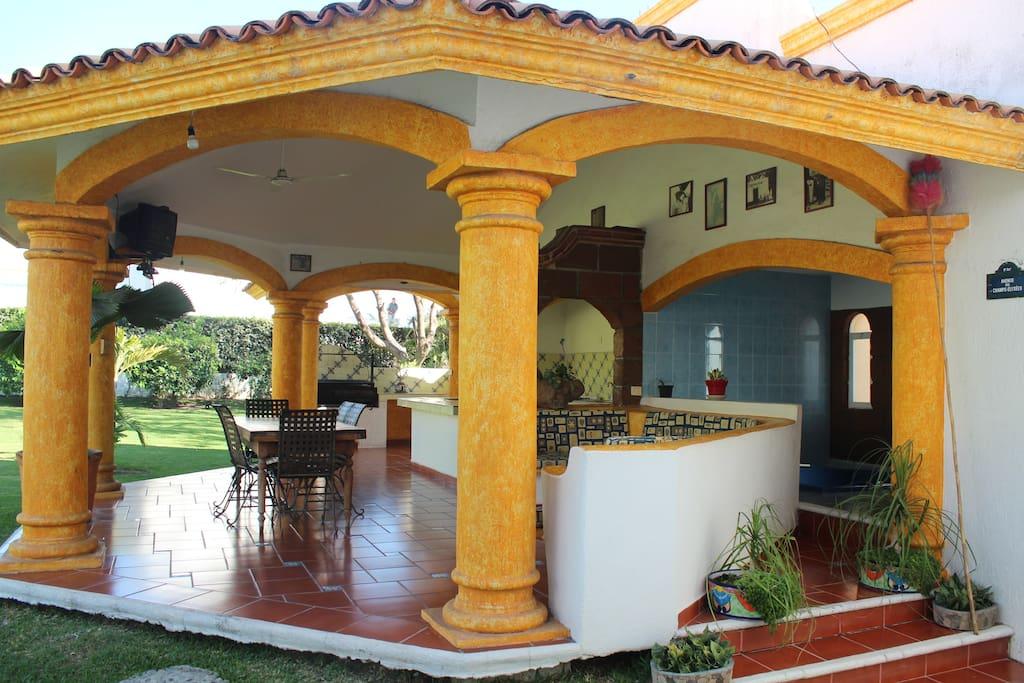 Terraza cómoda y amplia que cuenta con sala, asador, mesa y una cocineta para una estancia agradable.
