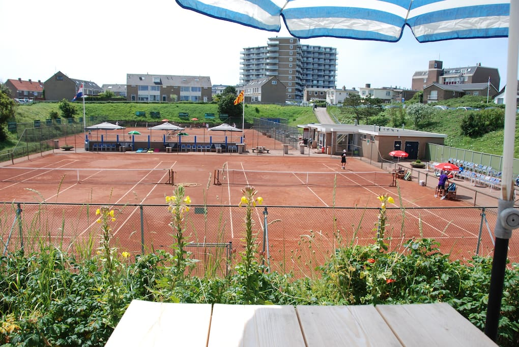 Zonnig terras met uitzicht op lager gelegen tennisbaan