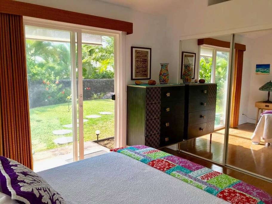 Guest bedroom with private entry sliding glass door for lots of fresh air that leads to tropical garden and covered lanai.