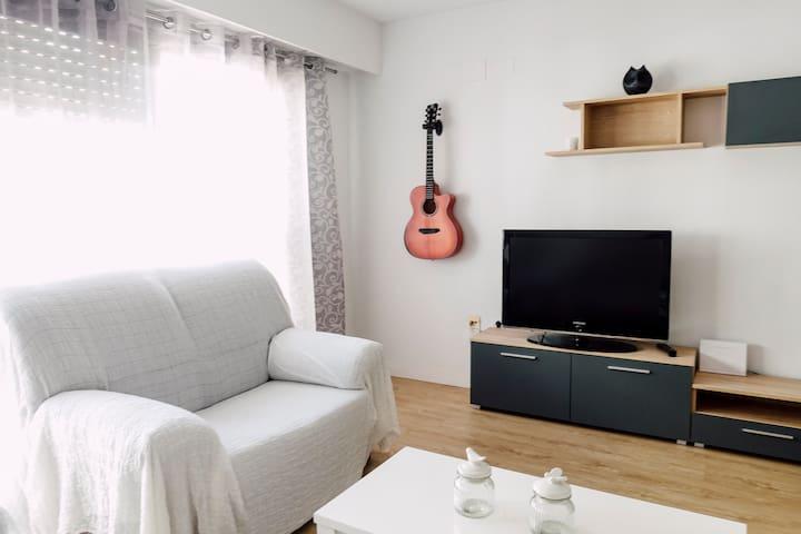 Salón principal, televisión y guitarra acústica.