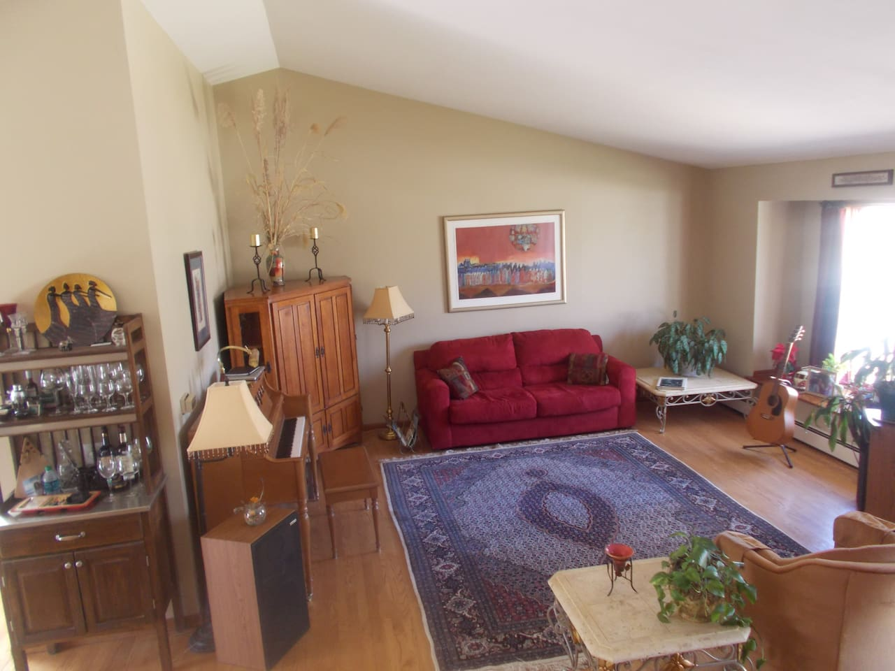 Comfortable and beauitful living room with valued ceiling, stereo and piano.