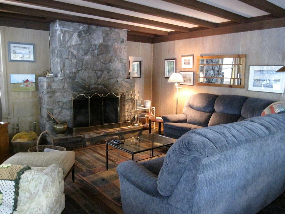 Main cottage's living room - big wrap-around couch, working stone fireplace, salvaged wooden floors.