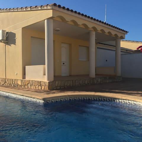 Fachada frontal del chalet con porche y piscina.