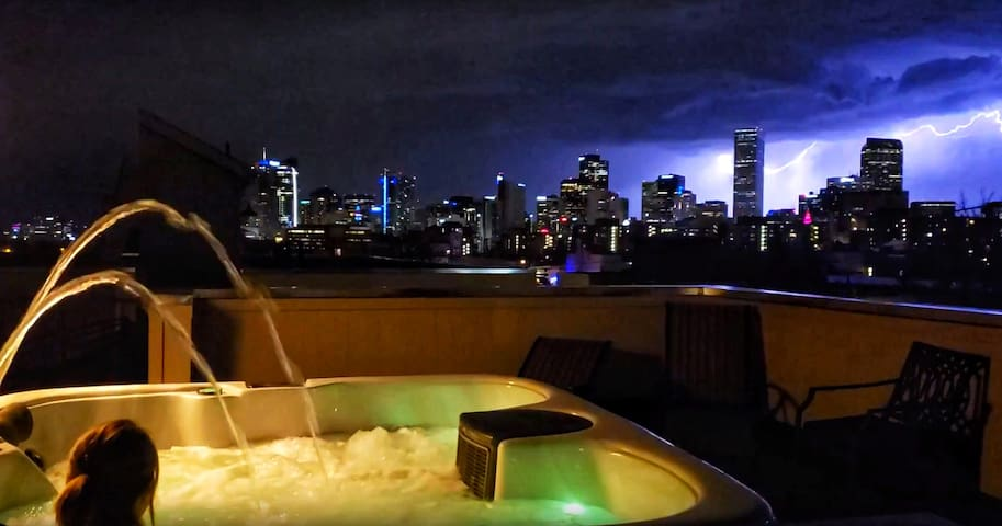 hot tub on the roof with a lightning storm behind the Denver skyline!