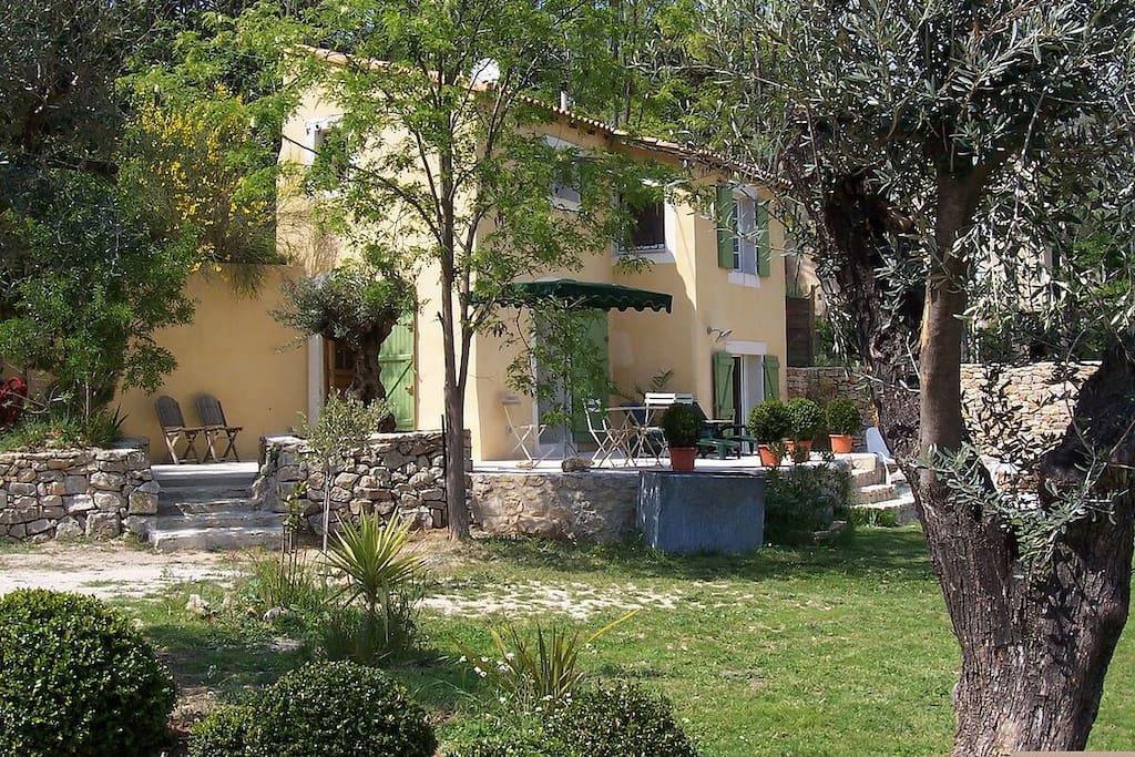 La jardin avec terrasses, salon de jardin et table à manger avec parasol.