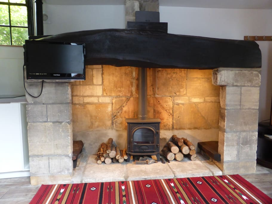 Log burner in period fireplace with wall mounted TV
