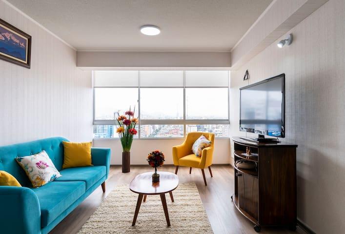 Acogedora sala, incluye televisión con ChromeCast (pie a streaming diverso), señal abierta full HD, cuenta con muebles estilo vintage, mesa de centro, floreros, iluminación completa en día y noche y tiene una vista amplia de la ciudad.