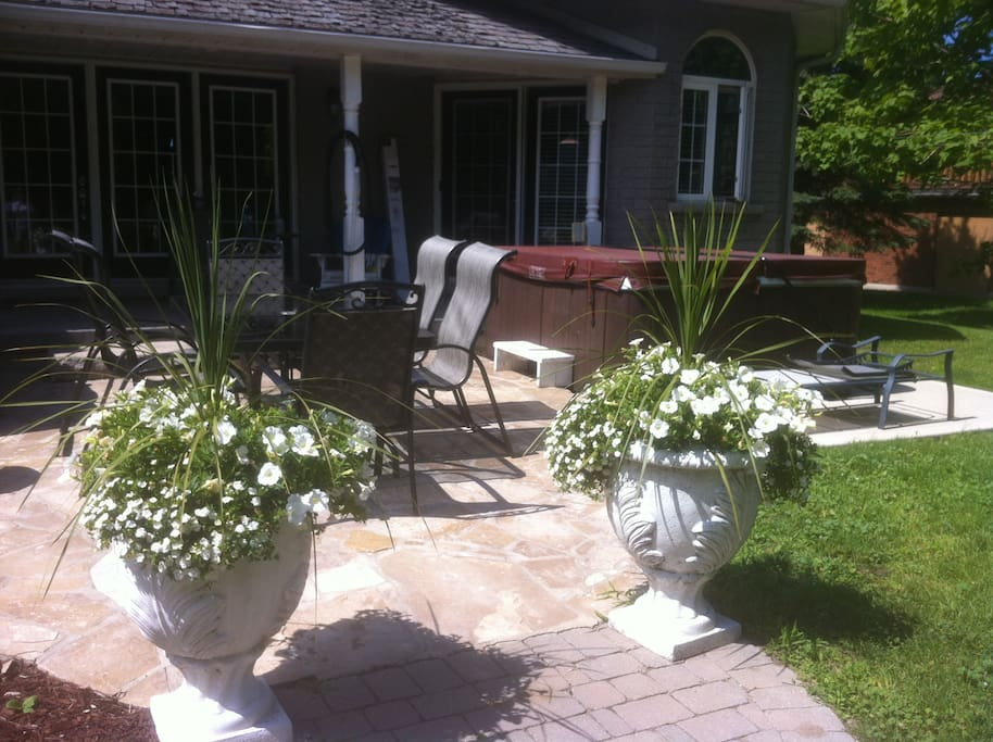 Backyard stone patio with 6 chair patio set, 4 burner bbq and hot tub