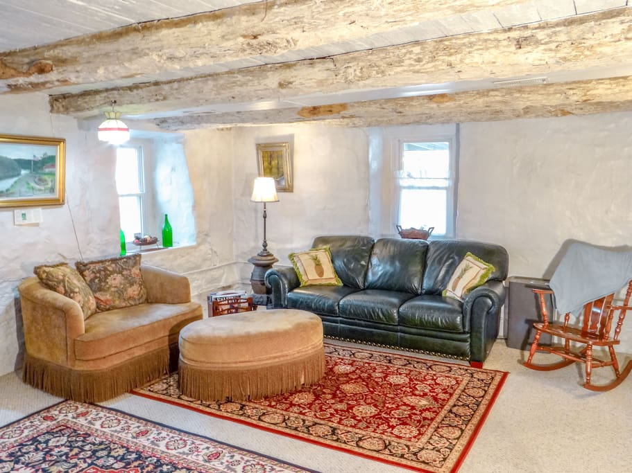 Overstuffed couches highlight the massive stone walls and whitewashed hewn logs, making a wonderful place talk and share wine.