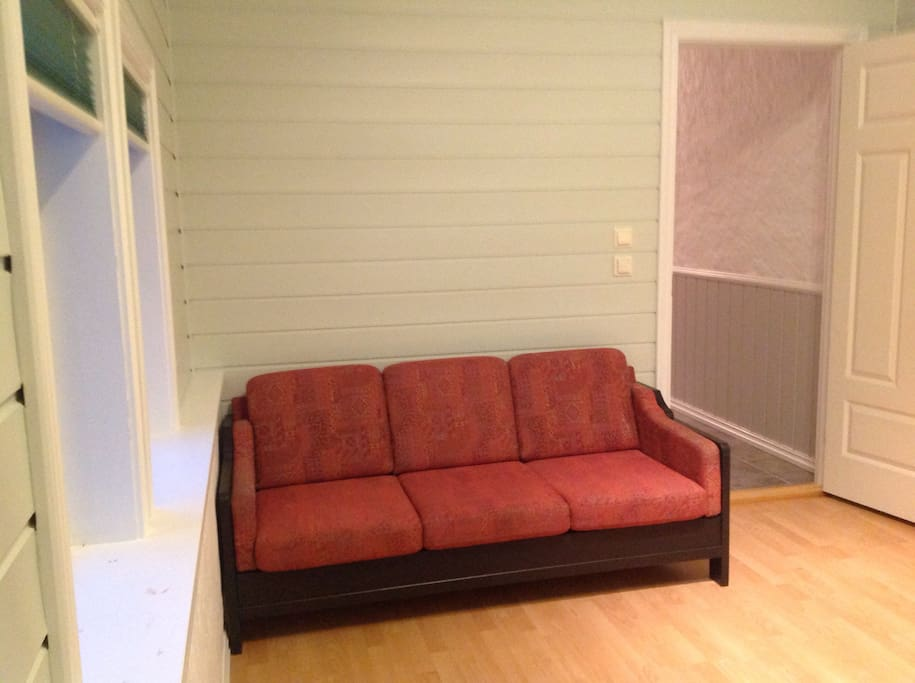 Lyst og trivelig rom med dobbeltseng og sofa.