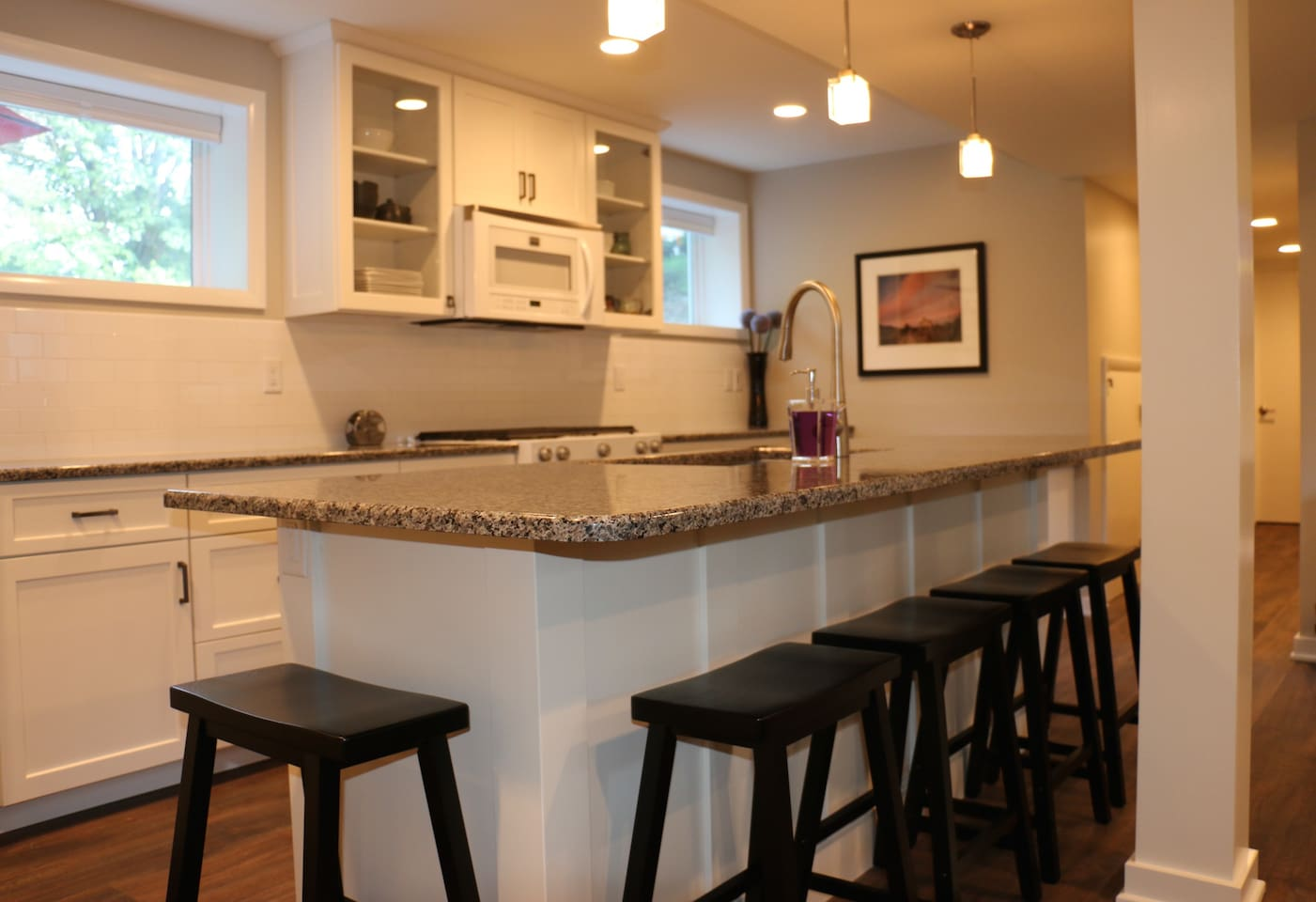 A large granite island serves as the centerpiece for the open kitchen/living room floor plan.