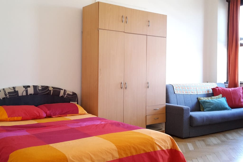 On this wall, there is a double bed, wardrobe and a couch which turns in to a double  bed.