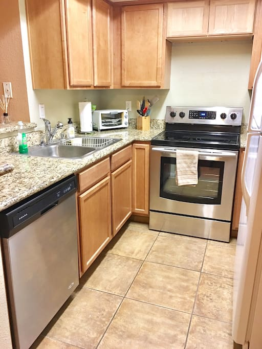 Kitchen with stove, dishwasher, fridge, coffee maker, roster and air-fryer.