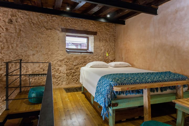 Comfortable hand-crafted wooden queen-sized bed with cotton individual pocket-spring mattress.