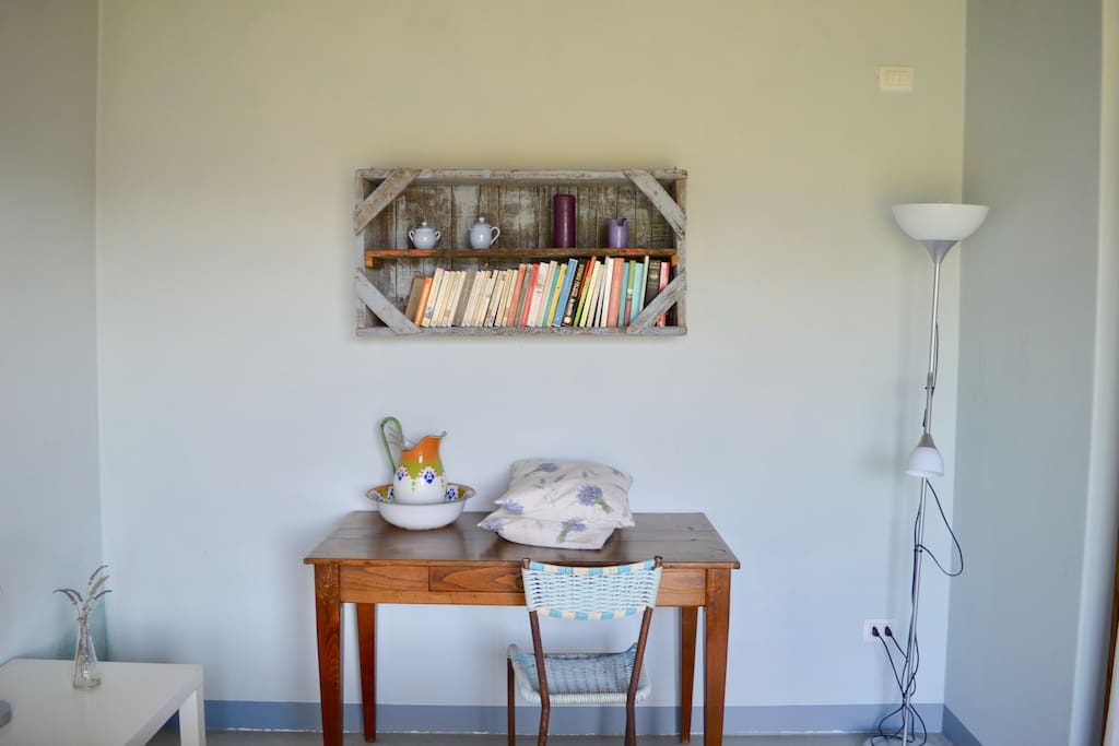 Bedroom with an old Tuscan table, and a book shelf made with an old box used for grape's and olive's harvest