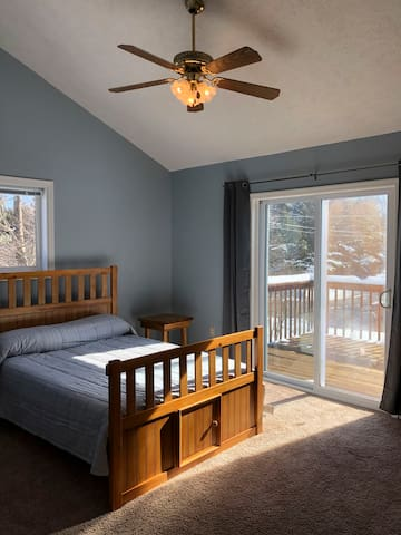 Front bedroom upstairs with full memory foam mattress, private balcony, massive closet, ceiling fan, and cathedral ceiling.