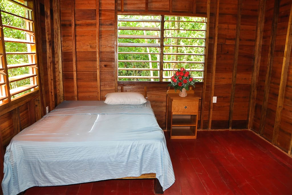 The double bed with direct view on the jungle.
