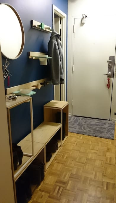 Entryway into the apartment, with coat hooks and shoe storage