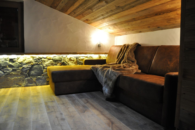 Des matériaux de prestige, grand canapé, mur en pierres locales, parquet chêne
