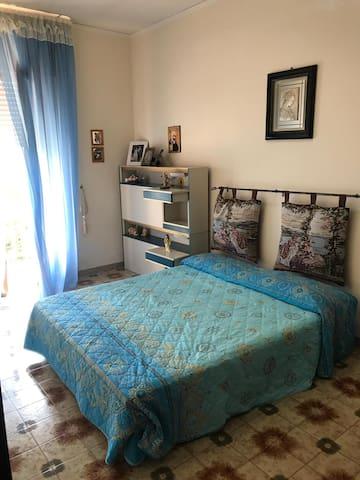 Camera da letto con letto matrimoniale e balcone su giardino