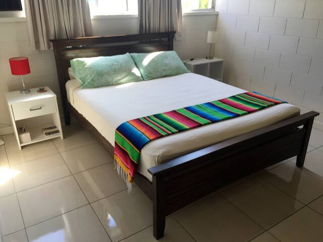 Queen bed with firm mattress and 100% cotton bedding. Window unit aircon, ceiling fan, and built-in wardrobe.