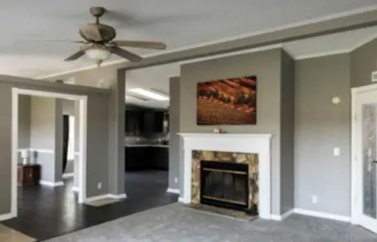 Large living room with wood burning fireplace and large LED TV with streaming services and WiFi internet.