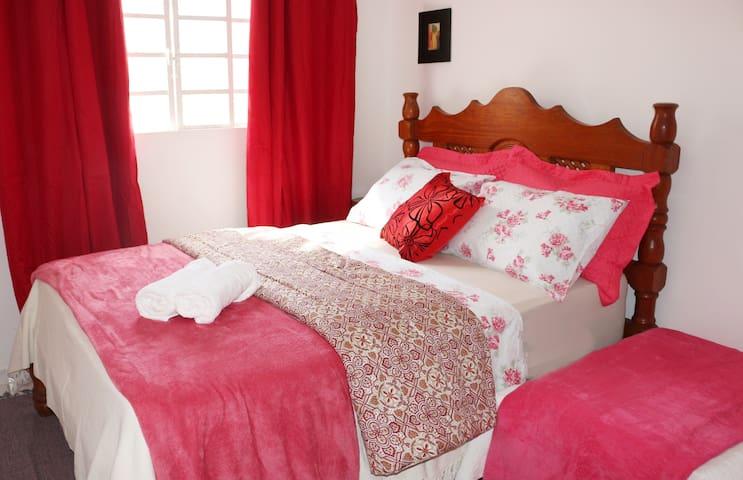 Quarto com cama casal e uma cama de  solteiro auxiliar, com   ar condicionado.