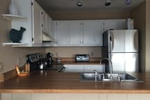 Kitchen is equipped with brand new stainless steel appliances (new dishwasher and hood not pictured) and all ammenities (plates, silverware, Keurig machine, etc.)