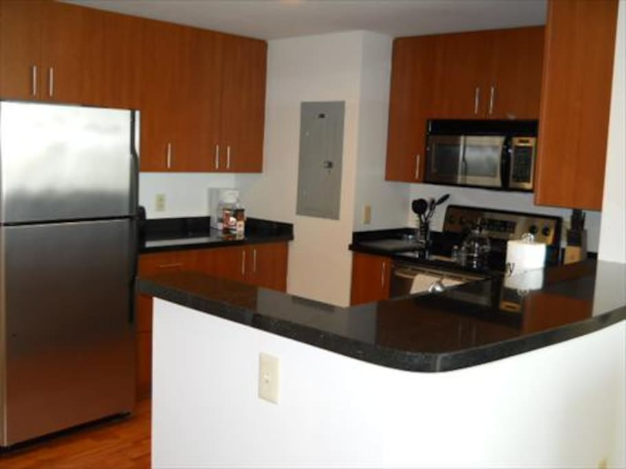 Fully equipped kitchen with stainless steel appliances, pots, pans, and dishes.
