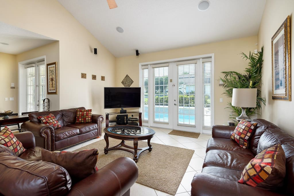 Living area with 65-inch LCD TV, PlayStation 3, surround sound system & sleeper sofa