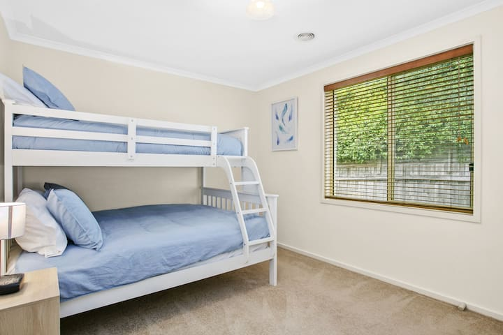 Triple bunk: double base with single on top is on the 3rd bedroom. situated off a hallway with convenient sliding door for noise reduction at kids' bedtime. This room has carpet and a portable fan. A portacot is also provided (BYO linen).