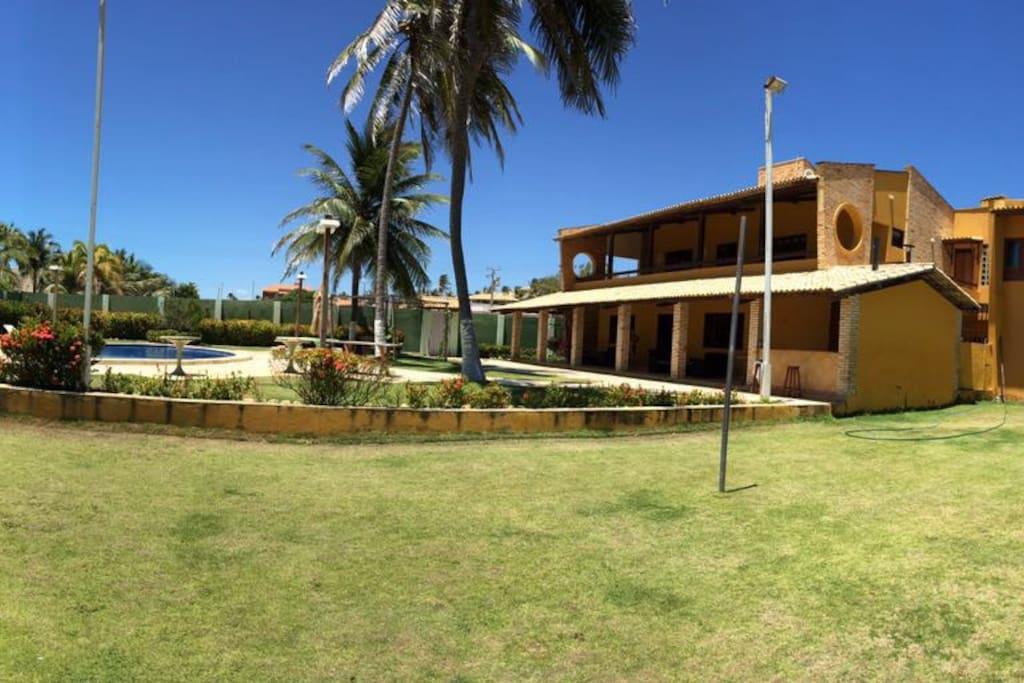 Vista campo de futebol, casa e piscina.